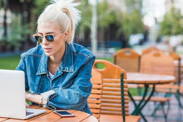 Młoda modna kobieta używa laptop przy outdoors Darmowe Zdjęcia