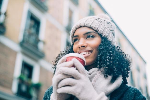 Młoda murzynka pije kawę wędruje po ulicach madrytu w zimie Premium Zdjęcia