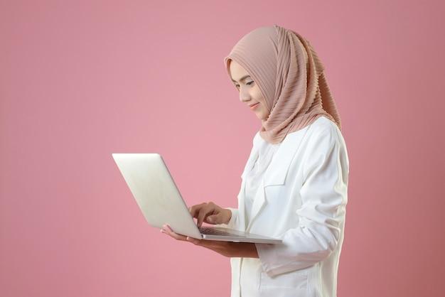 Młoda muzułmanka pracuje online przez laptop Premium Zdjęcia