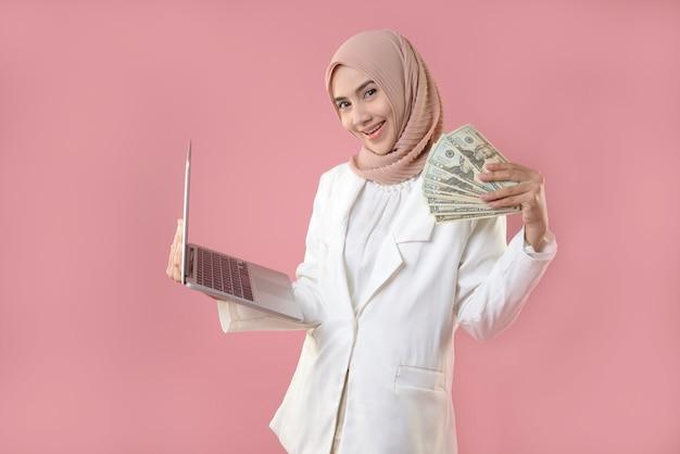 Młoda Muzułmanka Trzymać Pieniądze I Laptopa Premium Zdjęcia