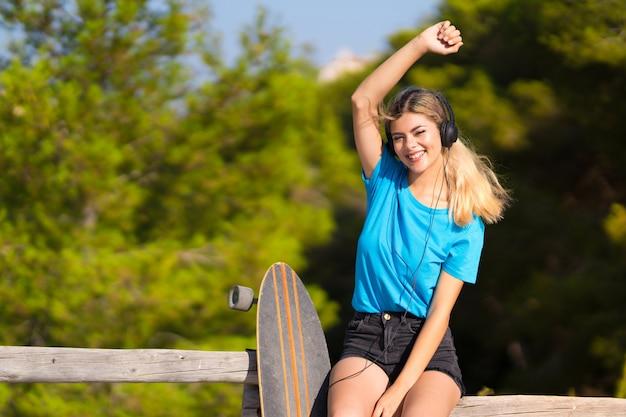 Młoda nastolatek dziewczyna z łyżwowym słuchaniem muzyka z hełmofonami przy outdoors Premium Zdjęcia