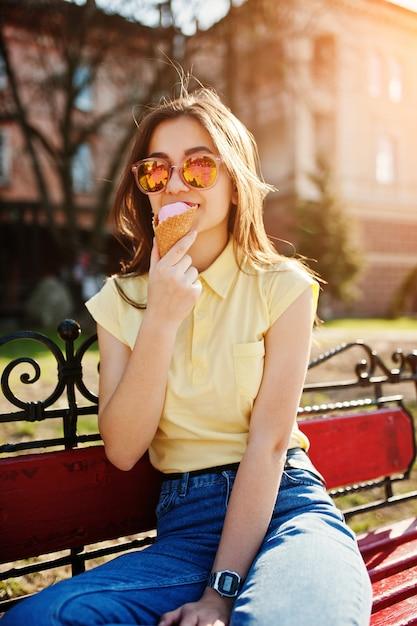 Młoda Nastolatka Siedzi Na ławce Z Lodami Pod Ręką, Nosić żółty T-shirt, Dżinsy I Okulary Przeciwsłoneczne. Premium Zdjęcia