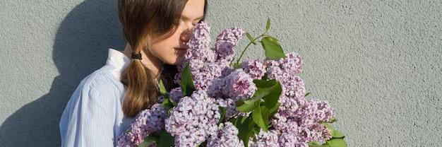 Młoda nastolatka z bukietem bzu w pobliżu szarej ściany Premium Zdjęcia