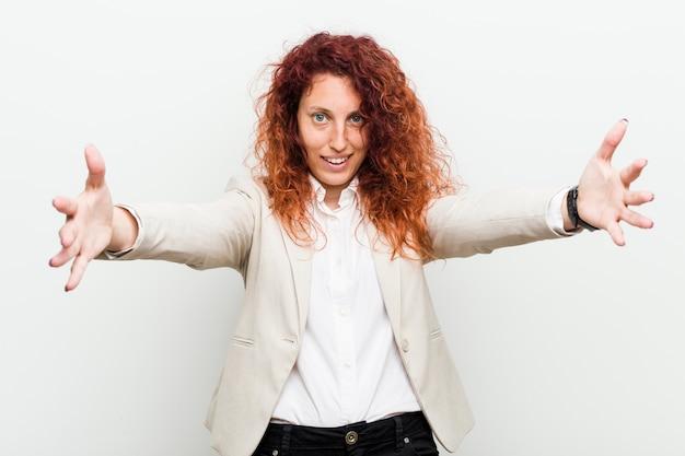 Młoda naturalna ruda kobieta biznesu czuje się pewnie, ściskając Premium Zdjęcia
