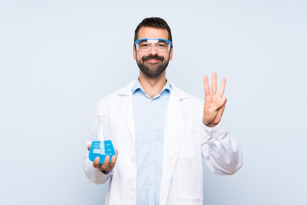 Młoda naukowa trzyma laborancka kolba nad odosobnioną ścianą szczęśliwą i liczy trzy z palcami Premium Zdjęcia