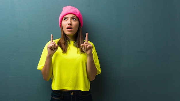 Młoda nowożytna kobieta zaskakująca wskazywać do pokazywać coś up Premium Zdjęcia