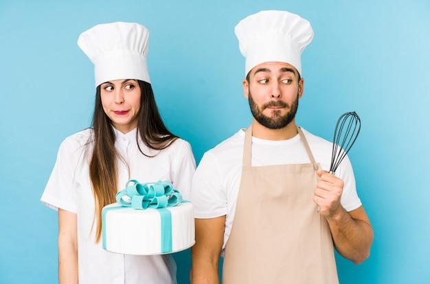 Młoda Para Gotuje Razem Ciasto Gryząc Paznokcie, Nerwowa I Bardzo Niespokojna. Premium Zdjęcia