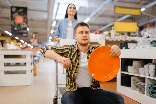 Młoda Para Jedzie Na Wózku W Sklepie Agd. Mężczyzna I Kobieta Kupują Artykuły Domowe Na Rynku, Rodzina W Sklepie Z Artykułami Kuchennymi Premium Zdjęcia
