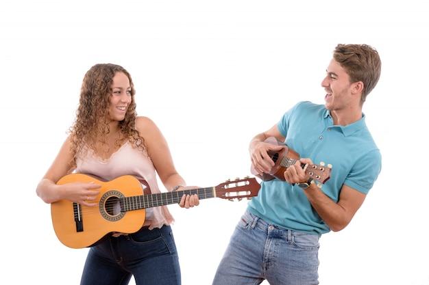 Młoda para kaukaska gra na gitarze i ukulele na białym tle Premium Zdjęcia