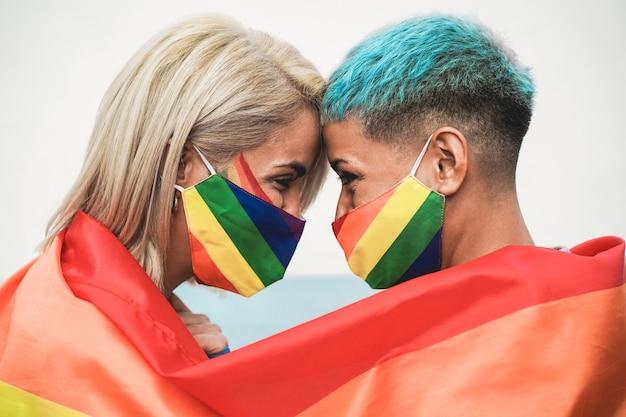 Młoda Para Kobiet Przytulających Się Pod Tęczową Flagą W Kolorowych Maskach Na Imprezie Dumy Gejowskiej Premium Zdjęcia