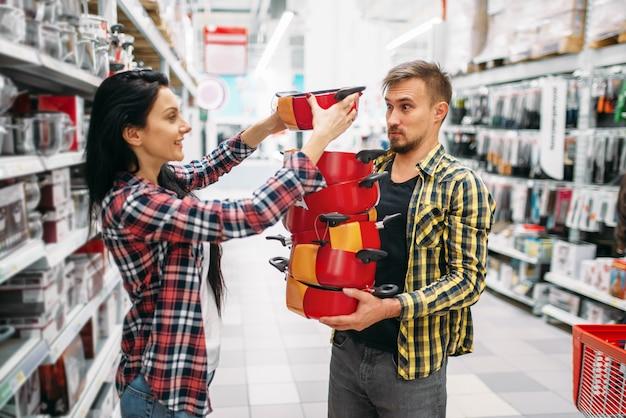 Młoda Para Kupuje Patelnie W Supermarkecie. Klienci Płci Męskiej I żeńskiej Na Rodzinne Zakupy. Mężczyzna I Kobieta Kupują Towary Do Domu Premium Zdjęcia