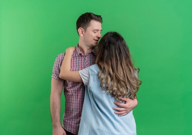 Młoda Para Mężczyzna I Kobieta W Ubranie Stojących Razem Szczęśliwi W Miłości Przytulanie Stojący Nad Zieloną ścianą Darmowe Zdjęcia