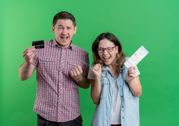 Młoda Para Mężczyzna I Kobieta W Ubranie Szczęśliwy Mężczyzna Trzyma Kartę Kredytową, Podczas Gdy Jego Dziewczyna Trzyma Bilety Lotnicze Szczęśliwa I Podekscytowana Stojąc Nad Zieloną ścianą Darmowe Zdjęcia