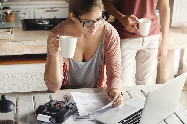 Młoda Para Oblicza Wydatki Rodzinne W Domu. Kobieta W Okularach Płacąca Rachunki Za Media Online, Pijąca Kawę Lub Herbatę, Siedząca W Kuchni Z Dokumentami I Kalkulatorem, Patrząc Na Ekran Laptopa Darmowe Zdjęcia