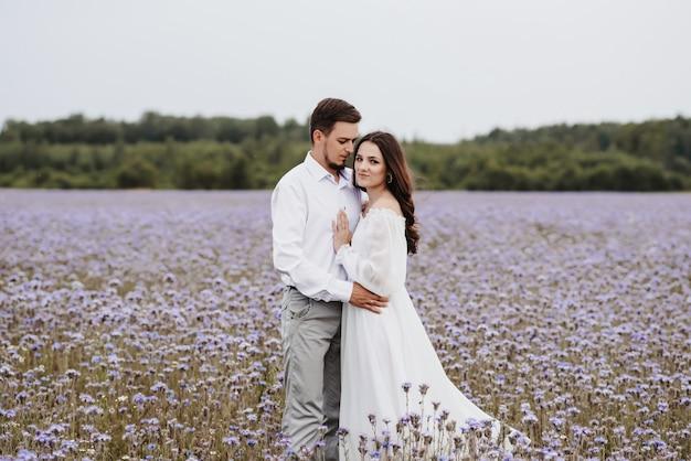 Młoda Para Piękny Stojący W Kwitnącym Fioletowym Polu Premium Zdjęcia