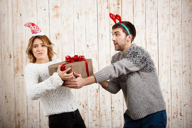 Młoda Para Piękny Walka O Prezent Na Boże Narodzenie Na Powierzchni Drewnianych Darmowe Zdjęcia