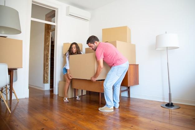 Młoda Para Pochodzenia Hiszpańskiego Wprowadza Się Do Nowego Mieszkania, Niosąc Kartony I Meble Darmowe Zdjęcia