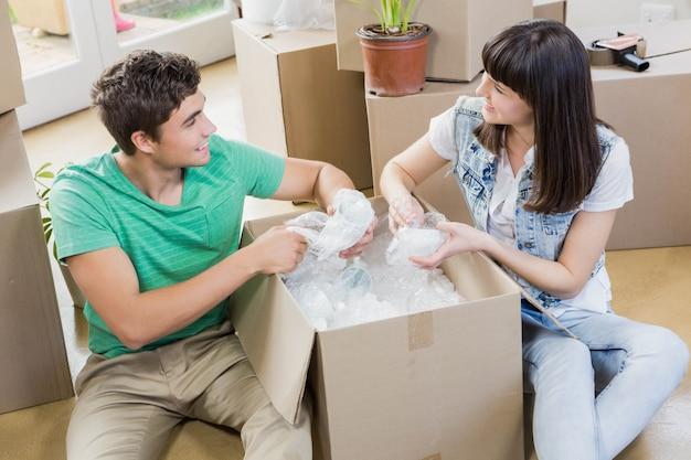 Młoda para pomaga sobie nawzajem podczas rozpakowywania kartonów w nowym domu Premium Zdjęcia