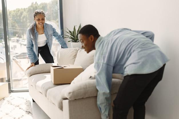 Młoda Para Przeprowadza Się Razem Do Nowego Domu. Afroamerykanin Para Z Kartonów. Darmowe Zdjęcia