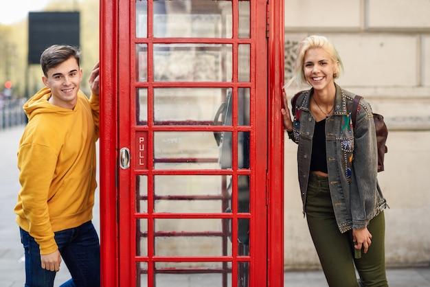 Młoda para przyjaciół w pobliżu klasycznej brytyjskiej czerwonej budki telefonicznej Premium Zdjęcia