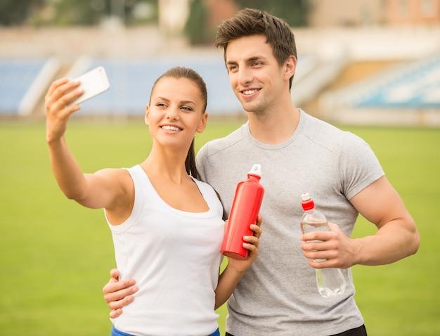 Młoda para robi selfie zdjęcie na stadionie. Premium Zdjęcia