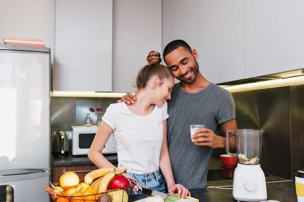 Młoda Para Robi śniadanie W Kuchni. Mężczyźni I Kobiety W T-shirtach Obejmujących Się, Gotują Razem, Para Przytulająca Się Z Uśmiechniętymi Twarzami Darmowe Zdjęcia