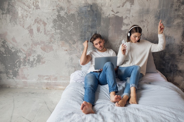Młoda Para Siedzi Na łóżku W Domu W Swobodnym Stroju, Zajęty Mężczyzna Pracujący Na Własny Rachunek Na Laptopie, Kobieta Słuchająca Muzyki Na Słuchawkach, Spędzanie Czasu Razem Darmowe Zdjęcia