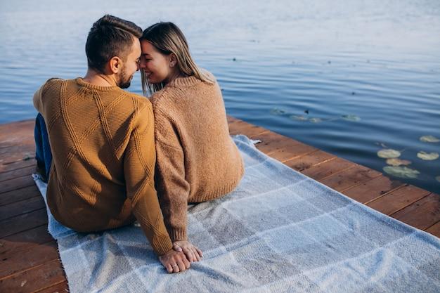 Młoda para siedzi na pokładzie mostu nad rzeką Darmowe Zdjęcia