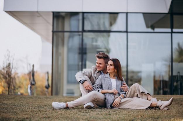 Młoda para siedzi na trawie przez budynek Darmowe Zdjęcia