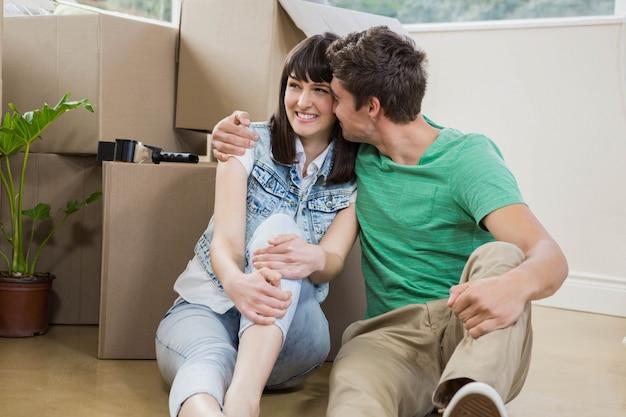 Młoda para siedzi razem na podłodze i uśmiecha się w swoim nowym domu Premium Zdjęcia