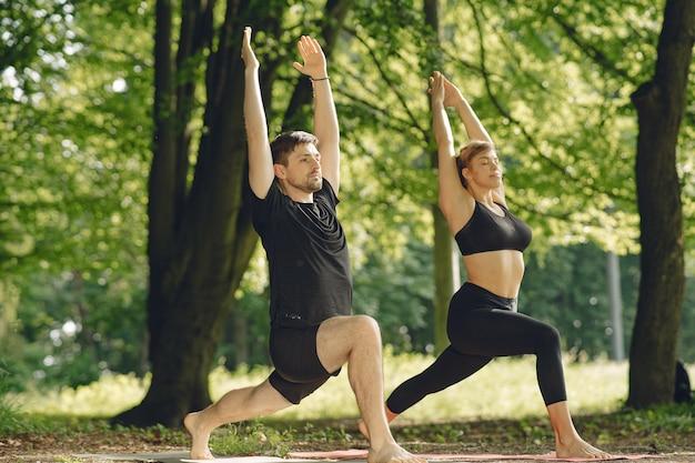 Młoda Para Sprawny Robi Joga Fitness. Ludzie W Letnim Parku. Darmowe Zdjęcia