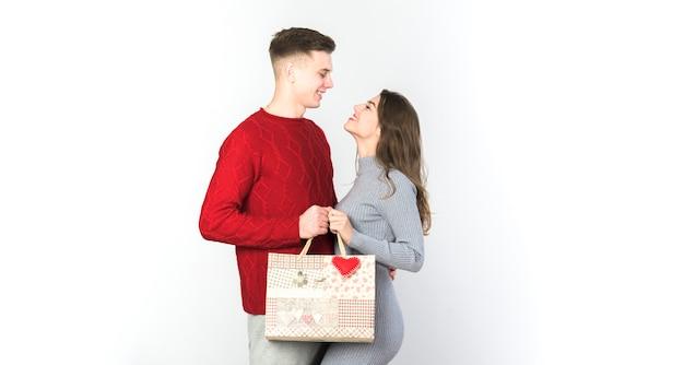 Młoda para stoi z torbą na prezent Darmowe Zdjęcia
