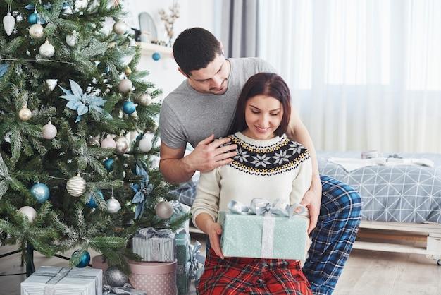 Młoda para świętuje boże narodzenie. mężczyzna nagle podarował żonie prezent. Premium Zdjęcia