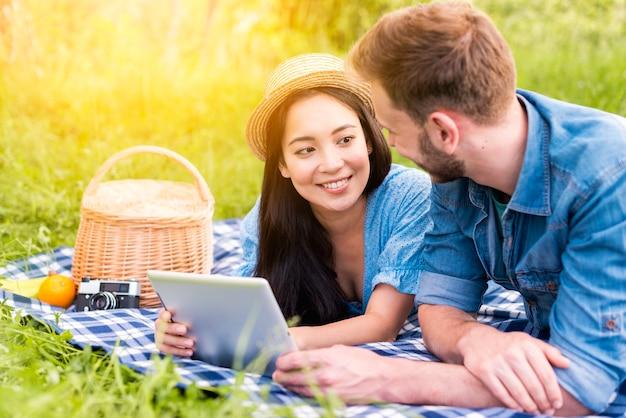 Młoda para uśmiecha się do siebie trzymając tablet na pikniku Darmowe Zdjęcia