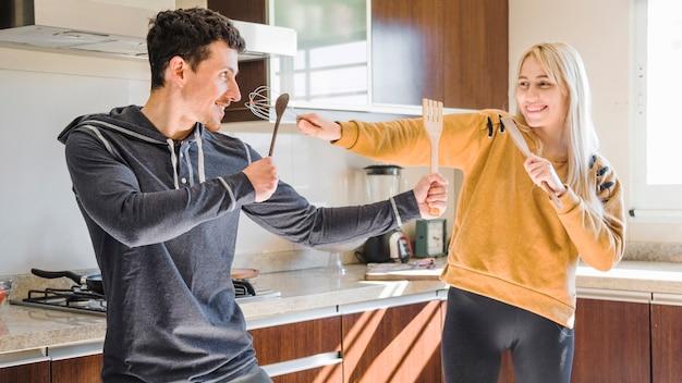 Młoda Para Walczy Z Drewnianą łopatką; łyżka I Trzepaczka W Kuchni Darmowe Zdjęcia