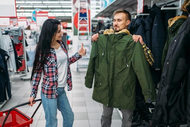 Młoda Para Wybiera Ciepłe Ubrania W Supermarkecie. Klienci Płci Męskiej I żeńskiej Na Rodzinne Zakupy. Mężczyzna I Kobieta Kupują Towary Do Domu Premium Zdjęcia