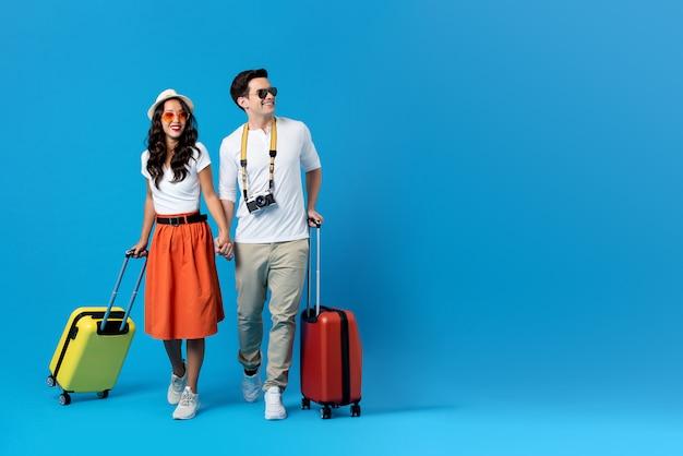 Młoda Para Wybiera Się Na Wakacje Z Kolorowymi Walizkami Premium Zdjęcia