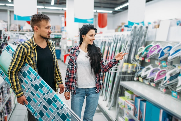 Młoda Para Wybiera żelazko Elektryczne W Supermarkecie. Klienci Płci Męskiej I żeńskiej Na Rodzinne Zakupy. Mężczyzna I Kobieta Kupują Towary Do Domu Premium Zdjęcia