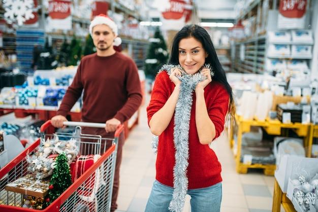 Młoda Para Z Wózkiem W Dziale Dekoracji świątecznych W Supermarkecie, Tradycja Rodzinna. Grudniowe Zakupy Noworoczne Lub świąteczne Premium Zdjęcia