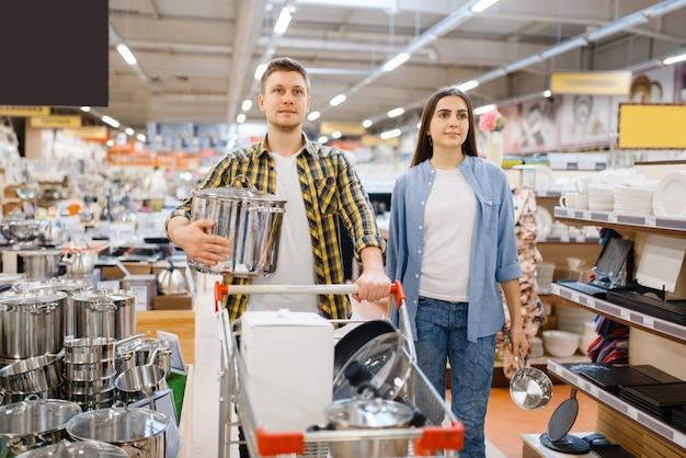Młoda Para Z Wózkiem W Sklepie Agd. Mężczyzna I Kobieta Kupują Artykuły Domowe Na Rynku, Rodzina W Sklepie Z Artykułami Kuchennymi Premium Zdjęcia