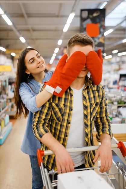 Młoda Para Zabawy, Zakupy W Sklepie Agd. Mężczyzna I Kobieta Kupują Artykuły Domowe Na Rynku, Rodzina W Sklepie Z Artykułami Kuchennymi Premium Zdjęcia