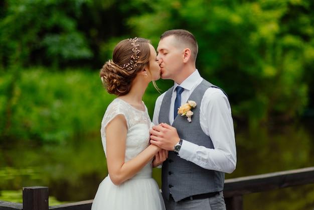 Młoda para zakochanych całowanie, pana młodego i panny młodej w sukni ślubnej Darmowe Zdjęcia