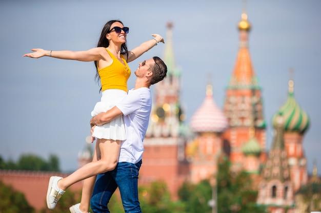 Młoda para zakochanych chodzenie w tle miasta st basils church Premium Zdjęcia