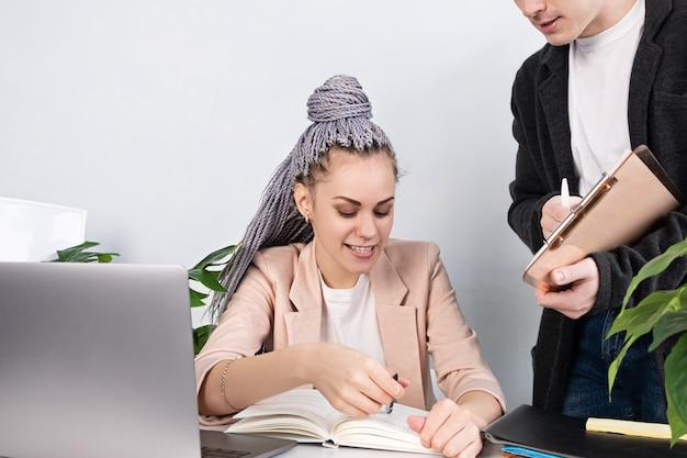 Młoda Pewna Siebie Liderka Wyjaśnia Coś Swojemu Asystentowi, Wskazując Na Notes, Siedząc W Biurze W Kurtce Przy Stole Roboczym I Laptopie. Pracownica, Kobieca Siła I Niezależność Premium Zdjęcia