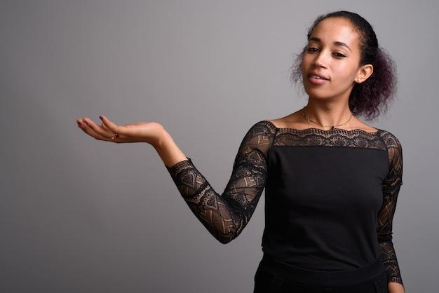 Młoda Piękna Afrykańska Kobieta Na Szaro Premium Zdjęcia