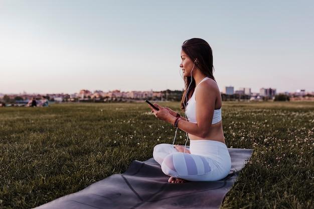 Młoda Piękna Azjatykcia Kobieta Relaksująca Po Jej Joga Praktyki Słucha Muzyka Na Słuchawkach I Telefonie Komórkowym. Joga I Koncepcja Zdrowego Stylu życia Premium Zdjęcia