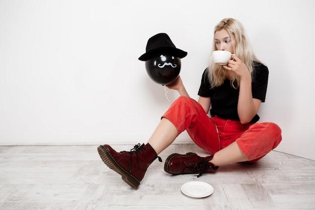 Młoda Piękna Blondynki Dziewczyna Trzyma Czarnego Baloon W Kapeluszowym Obsiadaniu Na Podłoga Pije Kawę Nad Biel ścianą. Darmowe Zdjęcia