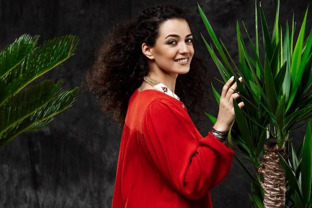 Młoda Piękna Brunetki Dziewczyna W Tropikalnych Roślinach Nad Szarości ścianą Darmowe Zdjęcia
