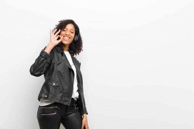Młoda piękna czarna kobieta słuchania muzyki w słuchawkach na sobie białą ścianę skórzanej kurtki Premium Zdjęcia