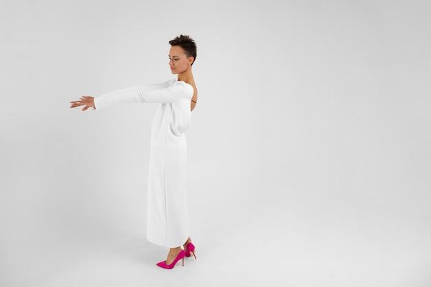Młoda Piękna Dziewczyna O Krótkich Ciemnych Włosach, W Długiej Białej Sukni Z Otwartymi Plecami, Stoi Z Powrotem Przed Kamerą I Wygląda Na Bok Premium Zdjęcia